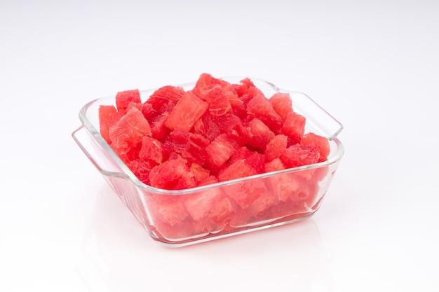 Cubes de pastèque disposés dans une vaisselle en verre avec fond blanc.