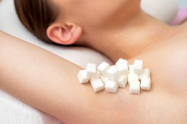 Cubes de sucre sur l'aisselle de la femme