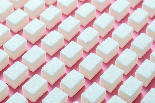 Cubes de sucre blanc raffiné de forme géométrique correcte sur un fond rose.