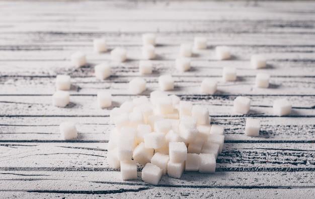 Cubes de sucre blanc sur une table en bois blanche. vue grand angle.