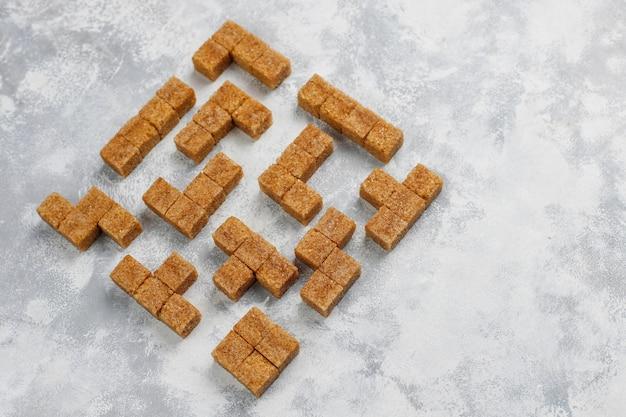 Cubes de sucre brun sur béton, vue de dessus