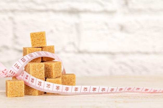 Cubes de sucre brun avec ruban à mesurer. concept de fitness