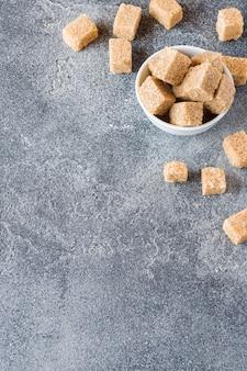 Cubes de sucre de canne brun sur béton. espace de copie
