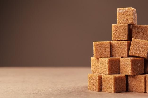 Cubes de sucre de canne brun sur fond brun clair