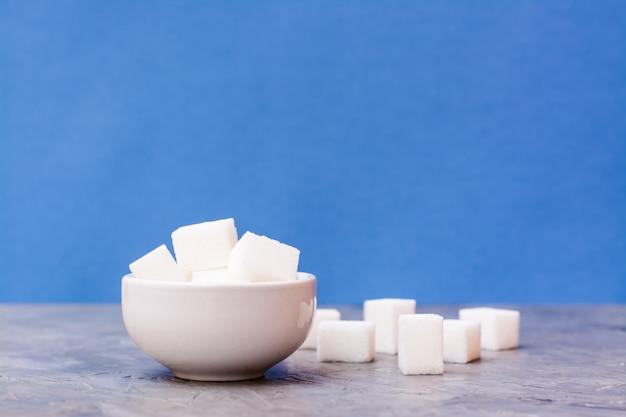 Cubes de sucre dans un bol blanc et à côté de la table sur un fond bleu