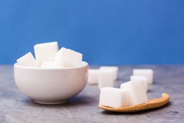 Cubes de sucre dans un bol blanc et une cuillère en bois sur une table sur un fond bleu