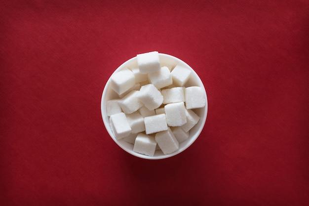 Cubes de sucre dans un bol sur fond rouge
