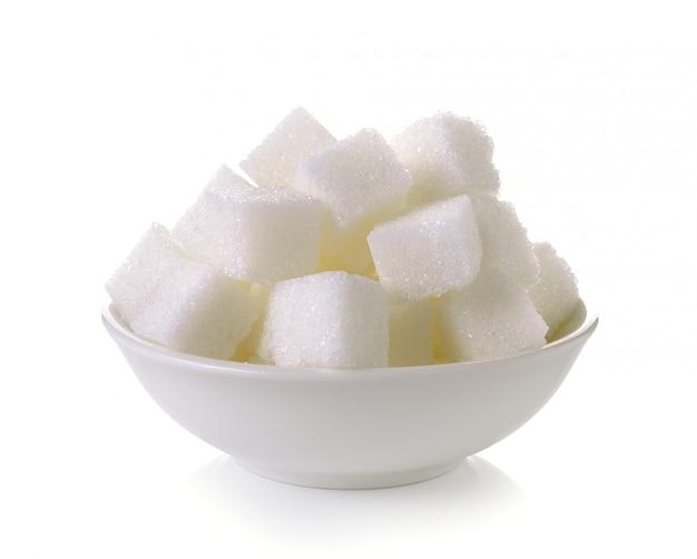 Cubes de sucre dans un bol isolé sur fond blanc