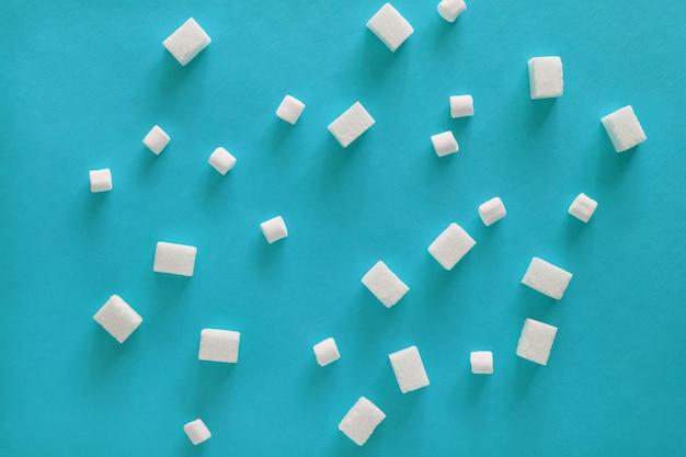 Cubes de sucre et guimauves sur fond bleu