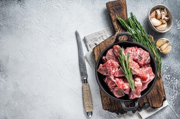 Cubes de viande en dés crus avec os dans une casserole
