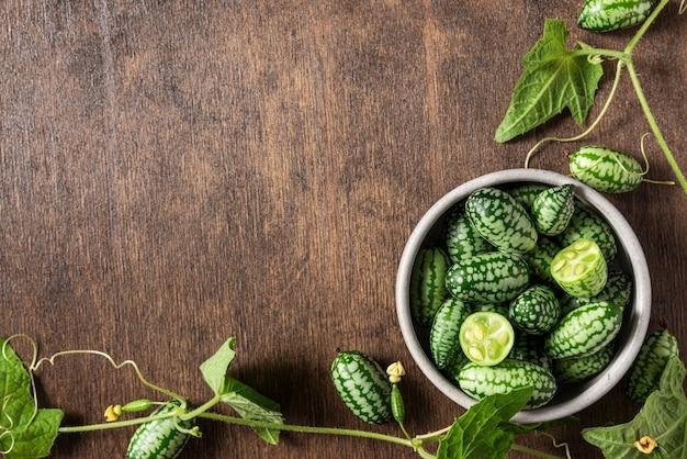 Cucamelon, melothria scabra ou melon de souris fraîchement récolté dans un bol avec des feuilles de plantes sur fond de bois