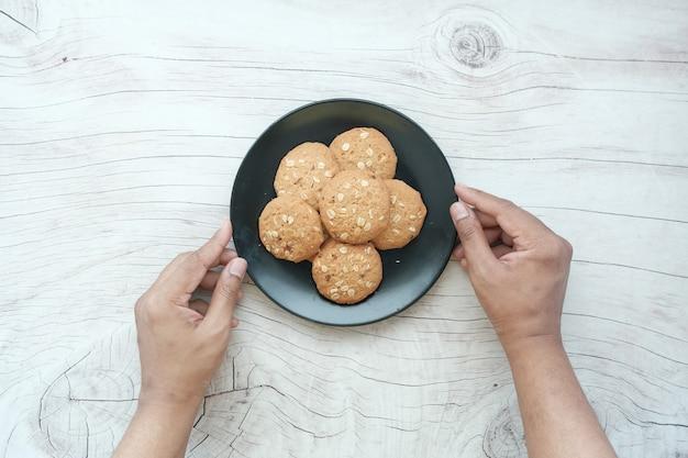Cueillir à la main des biscuits de repas entiers sur une surface en bois