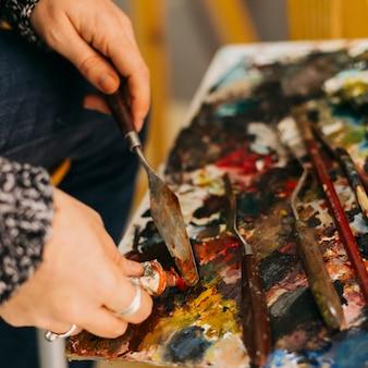 Cueillir les mains à l'aide d'une spatule pour prendre de la peinture