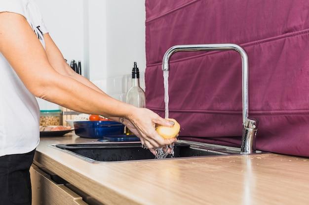 Cueillir les mains en lavant les pommes de terre crues dans l'évier