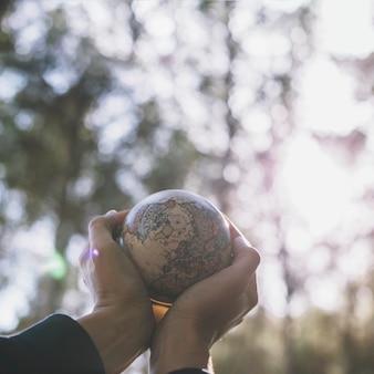 Cueillir les mains avec un petit globe dans la nature