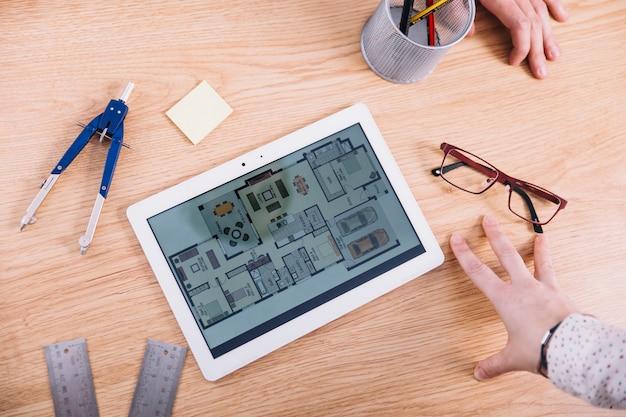 Cueillir les mains près de la tablette avec plan