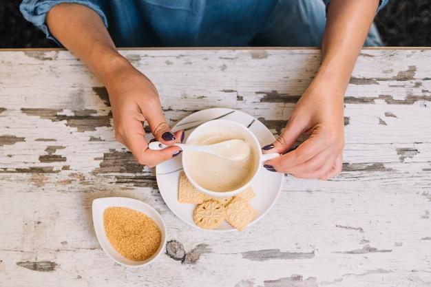 Cueillir les mains en remuant le café sur la table qui s'effrite