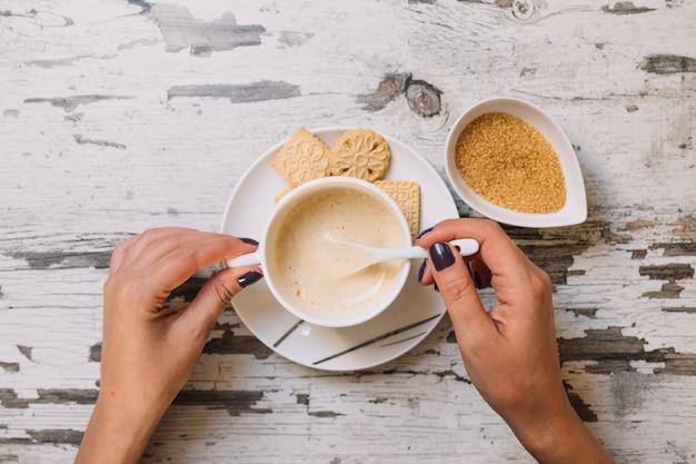 Cueillir les mains en remuant le sucre dans le café