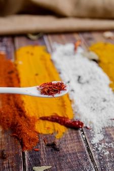 Cuillère blanche au safran sur fond d'épices colorées différentes. sélection d'épices variées. fermer. copiez l'espace.