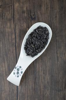 Cuillère blanche pleine de graines de tournesol noires saines placées sur une table en bois.