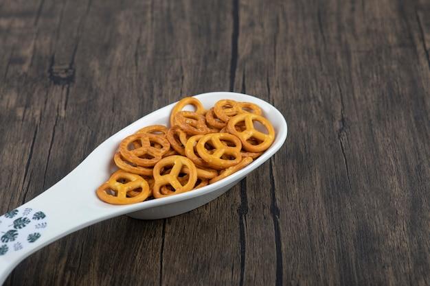 Cuillère blanche pleine de mini craquelins bretzels placés sur une table en bois.