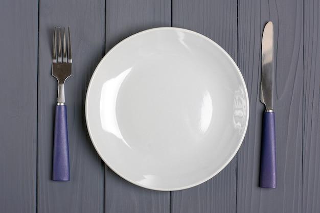 Cuillère bleu foncé, fourchette, couteau, assiette grise sur une table en bois grise