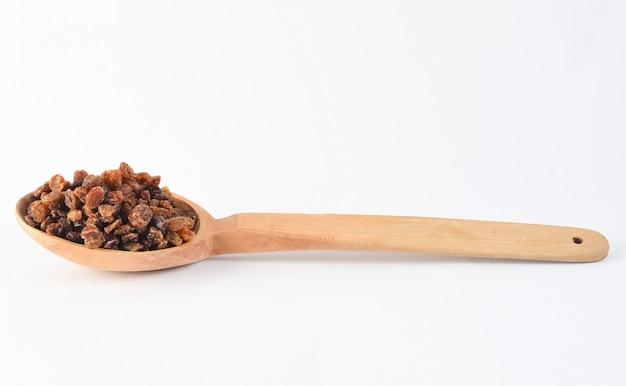 Cuillère en bois aux raisins secs sur fond blanc