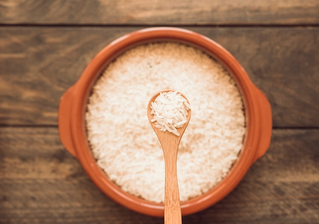 Cuillère en bois sur le bol de riz non cuit sur une table en bois