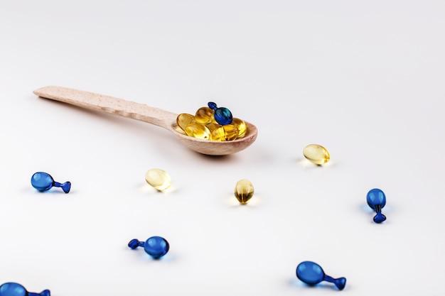 Cuillère en bois avec des capsules d'huiles et de vitamines pour les cheveux se trouve sur la table blanche