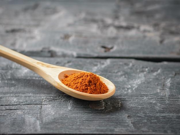 Cuillère en bois clair avec du poivre rouge concassé sur une table en bois foncé.