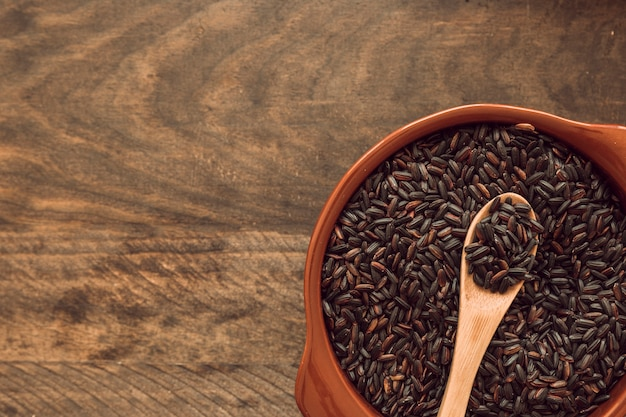 Cuillère en bois dans un bol de grain de riz brun sur une table en bois