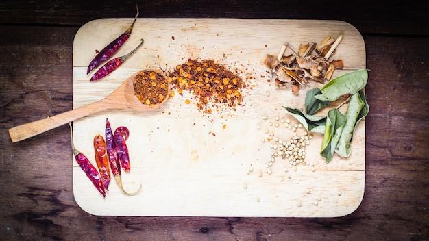 Cuillère en bois avec différents types d'ingrédients de cuisine thaïlandaise au quinoa et espace pour le texte sur fond de table en bois, vue de dessus