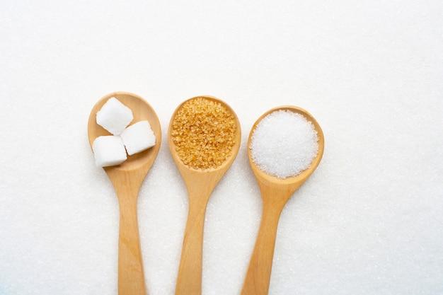 Cuillère en bois avec différents types de sucre sur du sucre granulé blanc.