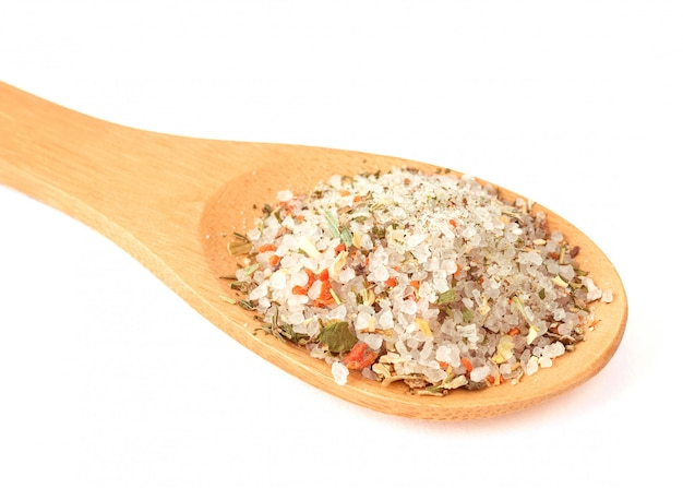 Cuillère en bois avec du sel de mer et un mélange d'épices isolé sur blanc.
