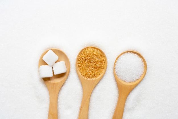 Cuillère en bois avec du sucre sur blanc