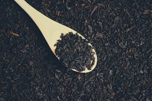 Cuillère en bois avec du thé noir saupoudré. tonifié.