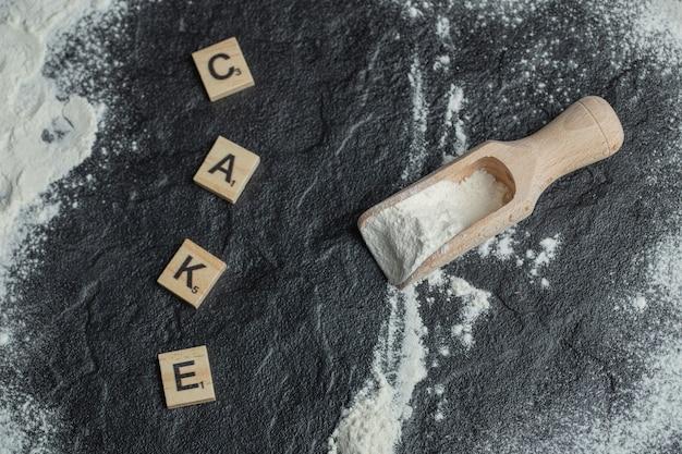 Une cuillère en bois avec de la farine et des lettres en bois.