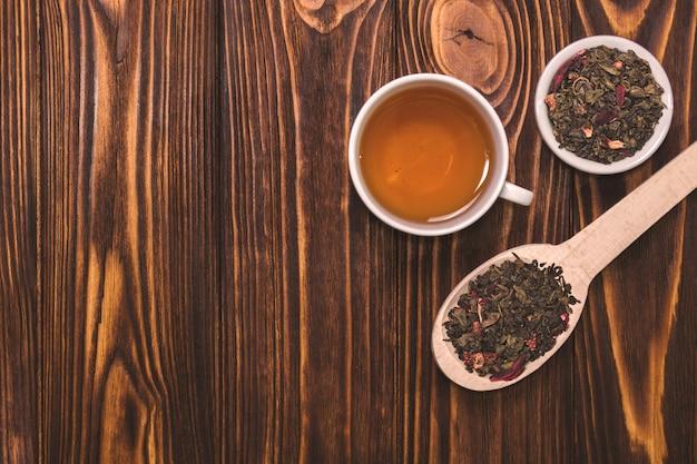 Une cuillère en bois avec des feuilles de thé séchées sur fond de bois