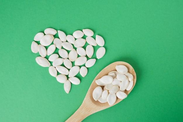Cuillère en bois et forme de coeur faite de graines de citrouille sur fond vert.