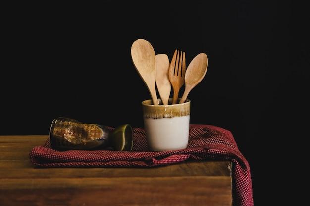 Cuillère en bois et une fourchette dans une tasse, concept nature morte.