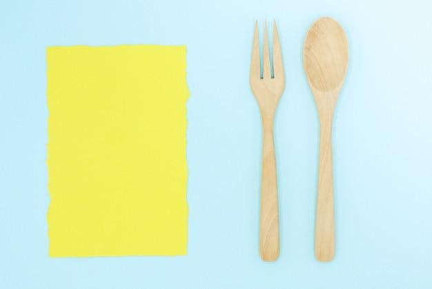 Cuillère en bois et une fourchette sur du papier bleu avec fond