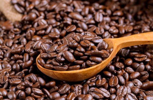Cuillère en bois de grains de café et un sac.