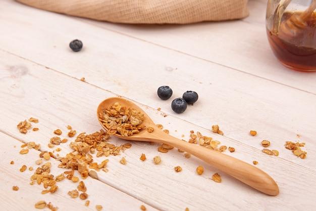 Cuillère en bois avec granola sur une table en bois.