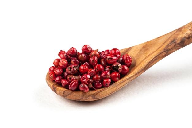 Cuillère en bois isolé de grains de poivre rouge isolé