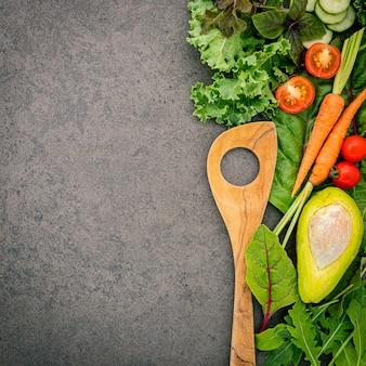 Cuillère en bois et légumes sur fond de pierre sombre.