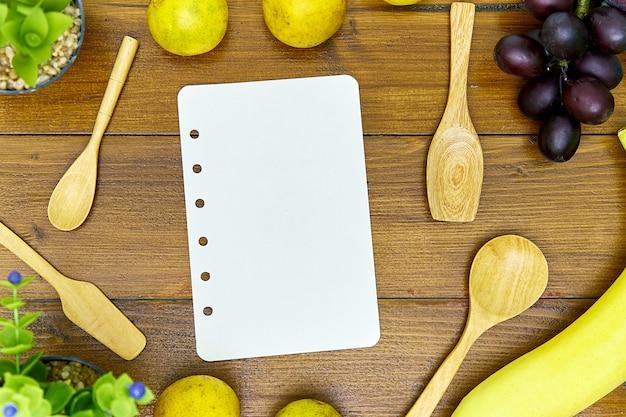 Cuillère en bois et livre de recette vierge sur table en bois