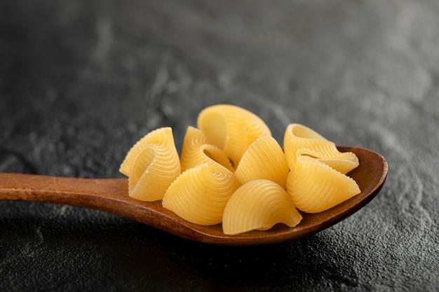 Une cuillère en bois de macaronis conchiglie non cuits.