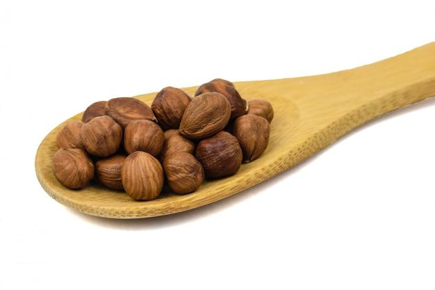 Cuillère en bois marron aux noisettes isolé sur fond blanc.