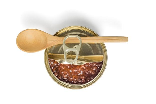 Cuillère en bois sur un pot ouvert avec du caviar rouge isolé sur une surface blanche