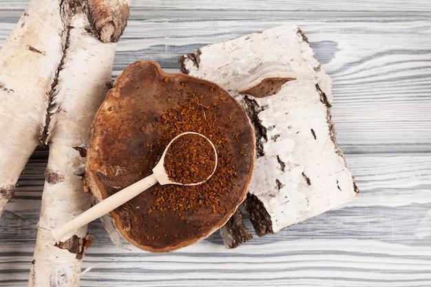 Une cuillère en bois avec de la poudre de thé chaga sèche repose sur un champignon de bouleau naturel à côté de l'écorce de bouleau.